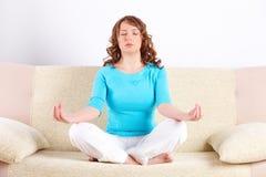 Mujer joven que hace ejercicio de la yoga en el sofá Imágenes de archivo libres de regalías