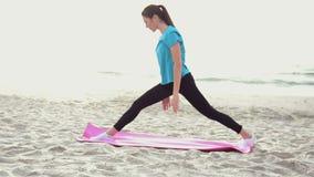 Mujer joven que hace ejercicio de la yoga en la playa de la arena del verano en la salida del sol metrajes