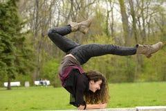 Mujer joven que hace ejercicio de la yoga en un parque Imagenes de archivo