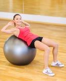 Mujer joven que hace ejercicio en bola de la aptitud Imagen de archivo