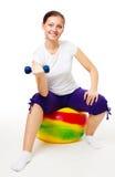 Mujer joven que hace ejercicios con la bola y el dumbell Imagenes de archivo