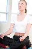 Mujer joven que hace ejercicios de la yoga Imagen de archivo