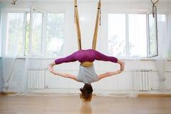 Mujer joven que hace ejercicios de la yoga aérea en hamaca Imágenes de archivo libres de regalías