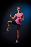 Mujer joven que hace ejercicios del paso Foto de archivo libre de regalías