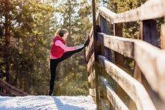 Mujer joven que hace ejercicios durante el entrenamiento del invierno afuera en tiempo frío de la nieve Fotografía de archivo