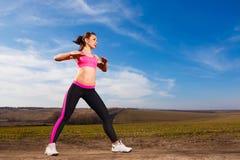 Mujer joven que hace ejercicios en fondo del cielo azul fotos de archivo