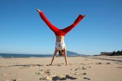 Mujer joven que hace ejercicios en la playa Fotografía de archivo