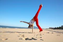 Mujer joven que hace ejercicios en la playa Imágenes de archivo libres de regalías