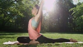 Mujer joven que hace ejercicios y que estira en parque soleado almacen de video