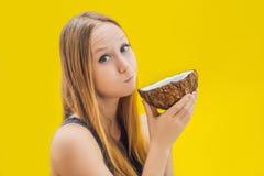 Mujer joven que hace el aceite que tira sobre fondo amarillo imagen de archivo