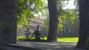Mujer joven que hace el asana de la yoga - janu-shirshasana