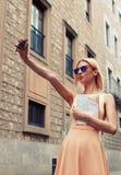 Mujer joven que hace el autorretrato con una cámara del teléfono celular mientras que disfruta de un día Fotografía de archivo libre de regalías