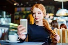 Mujer joven que hace el autorretrato usando smartphone Muchacha que hace el selfie Mujer en café Imagen de archivo libre de regalías