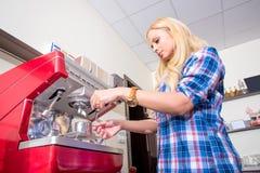 Mujer joven que hace el café Fotos de archivo