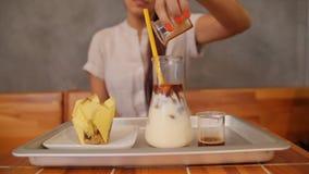 Mujer joven que hace el café helado 4K a cámara lenta almacen de video