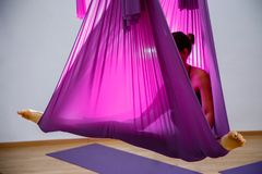 Mujer joven que hace el ejercicio aéreo de la yoga o la yoga antigravedad interior Fotos de archivo