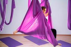 Mujer joven que hace el ejercicio aéreo de la yoga o la yoga antigravedad interior Foto de archivo