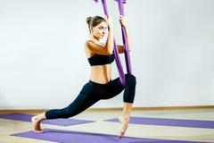 Mujer joven que hace el ejercicio aéreo de la yoga o la yoga antigravedad interior Fotografía de archivo libre de regalías
