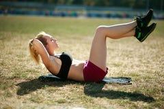 Mujer joven que hace el ejercicio de la aptitud de la prensa para los músculos de estómago Foto de archivo libre de regalías