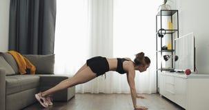 Mujer joven que hace el entrenamiento de la aptitud para la forma de vida sana en casa Forma de vida sana y del deporte almacen de video