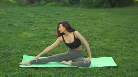 Mujer joven que hace el entrenamiento para estirar el cuerpo almacen de metraje de vídeo