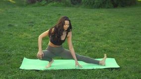 Mujer joven que hace el entrenamiento para estirar el cuerpo almacen de video