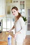 Mujer joven que hace el quehacer doméstico foto de archivo