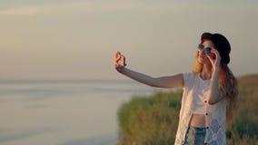Mujer joven que hace el selfie al borde de un acantilado cerca del río almacen de metraje de vídeo