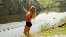 Mujer joven que hace el selfie al borde de un acantilado cerca del río almacen de video