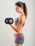 Mujer joven que hace el solo rizo de la pesa de gimnasia Imágenes de archivo libres de regalías