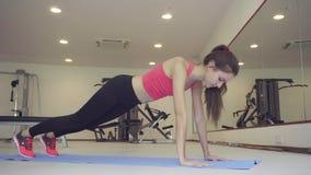 Mujer joven que hace el tablón del ejercicio en gimnasio La muchacha filtra los músculos de la prensa abdominal almacen de video