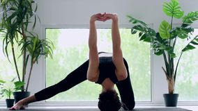Mujer joven que hace entrenamiento de la yoga en casa almacen de metraje de vídeo