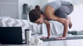 Mujer joven que hace entrenamiento de la yoga en casa metrajes