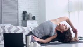 Mujer joven que hace entrenamiento de la yoga en casa almacen de video
