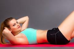 Mujer joven que hace entrenamiento del ABS en el piso Foto de archivo