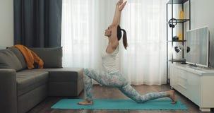 Mujer joven que hace entrenamiento en casa Muchacha de la aptitud que hace ejercicios de la yoga en la estera Forma de vida sana  metrajes