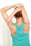 Mujer joven que hace estiramiento del hombro del uno mismo Imagen de archivo libre de regalías