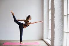Mujer joven que hace estirando ejercicio en la estera de la yoga Fotos de archivo