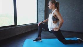 Mujer joven que hace estirando el tendón de la corva en la estera de la yoga en club de fitness almacen de video