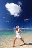 Mujer joven que hace estirar en la playa Fotografía de archivo libre de regalías