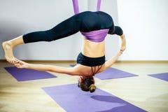 Mujer joven que hace estirar y la guita Ejercicio aéreo de la yoga o yoga antigravedad interior Aptitud, estiramiento, balanza, e Foto de archivo libre de regalías