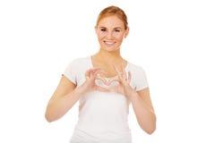 Mujer joven que hace forma del corazón con sus manos Imagen de archivo libre de regalías