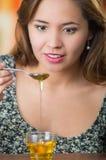 Mujer joven que hace frente a la cámara que sostiene la cuchara con el goteo de la miel en el pequeño vidrio en la tabla Fotos de archivo libres de regalías