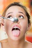 Mujer joven que hace frente a la cámara que sostiene la cuchara con el goteo de la miel sobre su lengua Imágenes de archivo libres de regalías