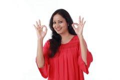 Mujer joven que hace gesto aceptable contra blanco Fotos de archivo