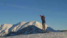 Mujer joven que hace girar alrededor contra las montañas del cielo y del invierno almacen de metraje de vídeo