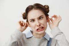 Mujer joven que hace la cara torpe que es bromista travieso con la boca torcida Actriz de sexo femenino que hace muecas en ropa c Imagenes de archivo