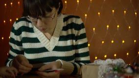 Mujer joven que hace la decoración para un árbol de navidad al lado de luces eléctricas amarillas almacen de metraje de vídeo