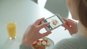 Mujer joven que hace la foto de su desayuno para los medios sociales metrajes