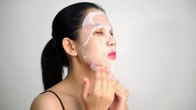 Mujer joven que hace la hoja facial de la máscara almacen de metraje de vídeo